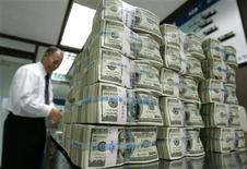 Работник отделения банка Korea Exchange Bank в Сеуле считает стодолларовые купюры, 9 октября 2008 года. Швейцарский трейдер Gunvor получил кредитную линию на сумму $800 миллионов для рефинансирования ранее полученных займов, сообщила компания. REUTERS/Jo Yong-Hak