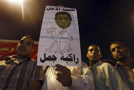 Protesters shout slogans against general prosecutor Abdel Maguid Mahmoud and members of the Mubarak regime at Tahrir Square, the focal point of the Egyptian uprising, in Cairo October 11, 2012. Egypt's president removed the general prosecutor from his post on Thursday, appeasing demonstrators who accused him of presenting weak evidence in a case against Mubarak-era officials accused of planning attacks on protesters last year. The poster shows Mahmoud's face pasted on a camel rider. REUTERS/Amr Abdallah Dalsh