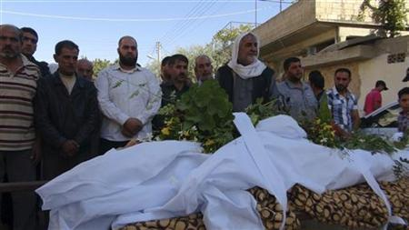 Residents pray during the funeral of youth Taha Naser, whom activists say was killed during shelling by forces loyal to Syria's President Bashar al-Assad, in Binsh, near Idlib October 12, 2012. REUTERS/Shaam News Network/Handout
