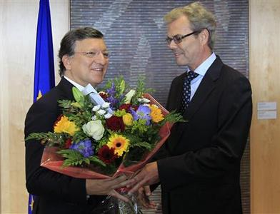 European Commission President Jose Manuel Barroso (L) receives flowers from Atle Leikvoll, Norway's Ambassador to the European Union, at the EC headquarters in Brussels October 12, 2012, after the European Union won the Nobel Peace Prize for its long-term role in uniting the continent, an award seen as morale boost for the bloc as it struggles to resolve its debt crisis. REUTERS/Yves Herman