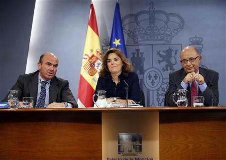 Spanish Economy Minister Luis de Guindos (L) speaks next to Treasury Minister Cristobal Montoro (R) and Deputy Prime Minister Soraya Saenz de Santamaria during their news conference after weekly cabinet meeting at Moncloa Palace in Madrid September 27, 2012. REUTERS/Sergio Perez
