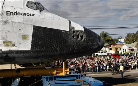 Crowds of people watch as the Space Shuttle Endeavour is transported on Manchester Avenue while being moved from Los Angeles International Airport to its retirement home at the California Science Center in Exposition Park, in Los Angeles, California October 12, 2012. REUTERS/Jonathan Alcorn