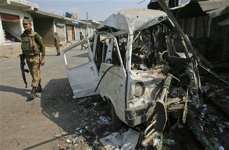 A paramilitary soldier walks past a damaged vehicle at the site of a suicide bomb attack in Darra Adam Khel, northwest Pakistan October 13, 2012. REUTERS/Khuram Parvez (PAKISTAN - Tags: POLITICS CIVIL UNREST CRIME LAW)