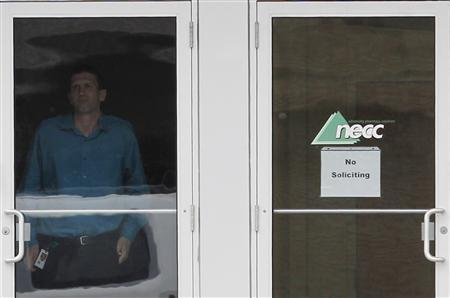 A security guard looks out from the front doors of pharmaceutical compounding company New England Compounding Center (NECC), a producer of the steroid methylprednisolone acetate, in Framingham, Massachusetts October 8, 2012. REUTERS/Jessica Rinaldi