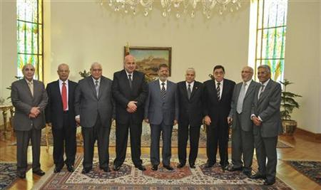 Egyptian President Mohamed Mursi (C), Vice President Mahmoud Mekky (4th L) and Chief investigator Abdel-Meguid Mahmoud (3rd R) pose for a photograph with unidentified personnel in Cairo October 13, 2012. REUTERS/Egyptian Presidency/Handout