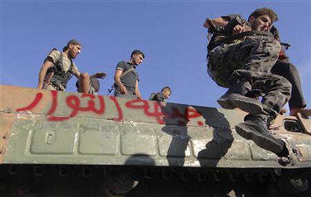 A member of the Free Syrian Army jumps form a military vehicle in Saraqib area near Aleppo in northern Syria October 12, 2012. The words on the vehicle read ''Revolution Front''. REUTERS/Stringer