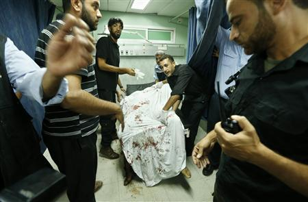 Palestinians wheel the body of a militant at a hospital, following an Israeli air strike in the northern Gaza Strip October 13, 2012. REUTERS/Mohammed Salem