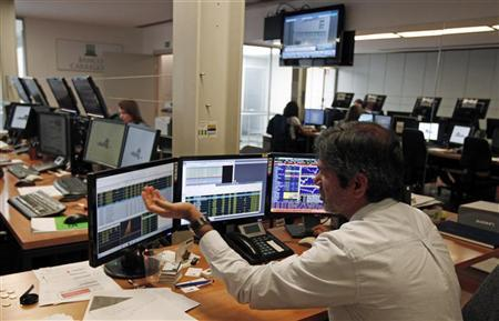 A trader gestures while watching screens in a trading room in Lisbon October 3, 2012. REUTERS/Jose Manuel Ribeiro