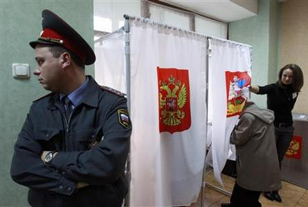 A police officer stands next to voting cabins during local elections in the Moscow suburb of Khimki October 14, 2012. REUTERS/Sergei Karpukhin (RUSSIA - Tags: POLITICS ELECTIONS)