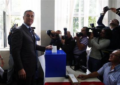 Milo Djukanovic (L), leader of the Democratic Party of Socialists (DPS) cast his vote during Montenegro's parliamentary elections in Podgorica, October 14, 2012. REUTERS/Marko Djurica