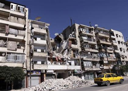 A taxi drives past a damaged building in the al Katerji Tariq district in Aleppo city in northern Syria October 14, 2012. REUTERS/Zain Karam