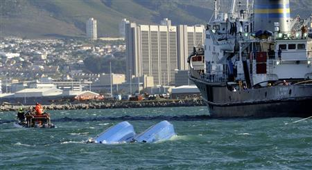 Rescuers tow a charter boat that capsized on a popular sight-seeing trip in Cape Town October 14, 2012. REUTERS/Stringer