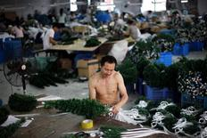 An employee makes plastic Christmas trees at the Zhongsheng Christmas Crafts factory in Yiwu, Zhejiang province in this September 13, 2012 file photo. REUTERS/Carlos Barria/Files