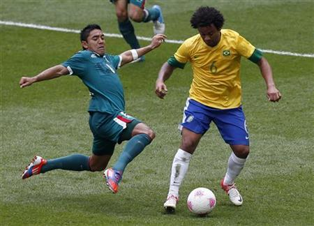 Mexico's Marco Fabian (L) attempts to tackle Brazil's Marcelo (R) during their men's soccer final gold medal match at Wembley Stadium during the London 2012 Olympic Games in this file photo taken August 11, 2012. REUTERS/Paul Hanna