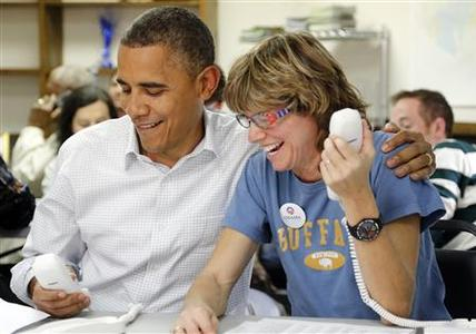 U.S. President Barack Obama (L) sits with campaign volunteer Suzanne Stern as he makes calls from a campaign office in Williamsburg, Virginia, October 14, 2012. REUTERS/Jonathan Ernst