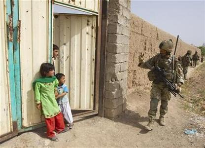 A British Army soldier of the 2nd Battalion, The Royal Gurkha Rifles waves to Afghan children during a patrol outside Patrol Base Chilli near the town of Lashkar Gah in Helmand province, southern Afghanistan, July 14, 2011. REUTERS/Shamil Zhumatov