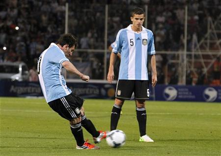 Argentina's Lionel Messi (L) kicks the ball to score his second goal against Uruguay as his teammate Fernando Gago looks on during their 2014 World Cup qualifying soccer match in Mendoza October 12, 2012. REUTERS/Enrique Marcarian