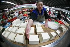 A vendor arranges tofu on her stall as she waits for customers at a market in Huaibei, Anhui province, October 15, 2012. China's annual consumer price inflation ticked down to 1.9 percent in September from August's 2.0 percent, official data showed on Monday, leaving plenty of room for further policy easing to shore up growth. REUTERS/Stringer