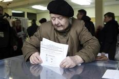 Женщина опускает бюллетень в урну на избирательном участке в Вильнюсе, 14 октября 2012 года. Литовская оппозиция готовится прийти к власти в понедельник, так как избиратели отвергли правительство, осуществляющее меры строгой экономии. REUTERS/Ints Kalnins