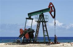 Нефтяная вышка на побережье в окрестностях Гаваны, 24 мая 2010 года. Нефть дешевеет на фоне ухудшения прогнозов мирового потребления, но опасения по поводу напряженности на Ближнем Востоке сдерживают падение цен. REUTERS/Desmond Boylan