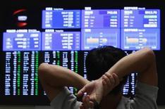 Посетитель Токийской фондовой биржи смотрит на экраны со значениями котировок, 26 сентября 2012 года. Азиатские фондовые рынки завершили торги разнонаправленно под влиянием данных из Китая и опасений за прибыль компаний в третьем квартале. REUTERS/Yuriko Nakao
