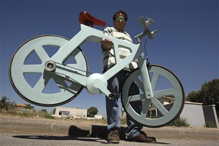 Israeli inventor Izhar Gafni holds his cardboard bicycle as he poses for a photo in Moshav Ahituv, central Israel September 24, 2012. The bicycle, made almost entirely of cardboard, has the potential to change transportation habits from the world's most congested cities to the poorest reaches of Africa, Gafni, an expert in designing automated mass-production lines and an amateur cycling enthusiast, says. Picture taken September 24, 2012. REUTERS/Baz Ratner