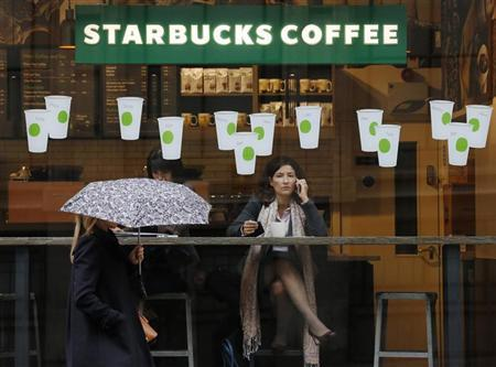 A woman carrying an umbrella walks in the rain past a Starbucks coffee shop in London October 8, 2012. Picture taken October 8, 2012. REUTERS/Luke Macgregor