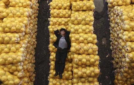 A vendor sleeps on packs of grapefruit at a market in Wuhan, Hubei province, October 15, 2012. China's annual consumer price inflation ticked down to 1.9 percent in September from August's 2.0 percent, official data showed on Monday, leaving plenty of room for further policy easing to shore up growth. REUTERS/Stringer