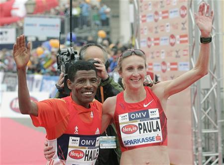 Ethiopian world marathon record holder Haile Gebrselassie and Paula Radcliffe of the UK wave to the crowd after the half marathon race during the Vienna City Marathon in Vienna April 15, 2012. REUTERS/Herwig Prammer