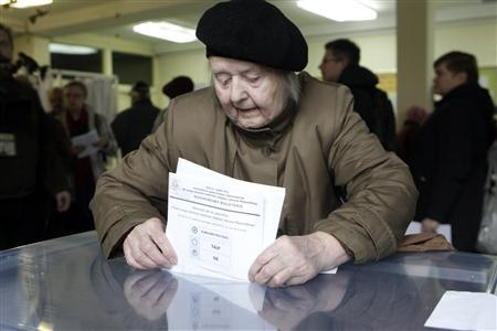 A woman casts her vote in Vilnius October 14, 2012. REUTERS/Ints Kalnins
