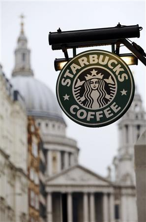 St Paul's Cathedral is pictured behind a signage for a Starbucks coffee shop in London October 8, 2012. Picture taken October 8, 2012. REUTERS/Luke Macgregor