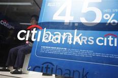 Женщина сидит рядом с рекламным щитом Citibank в Сеуле, 11 октября 2012 года. Прибыль Citigroup Inc в третьем квартале снизилась, так как компании пришлось списать $4,7 миллиарда, связанных с ее долей в брокерской компании, управляемой Morgan Stanley. REUTERS/Kim Hong-Ji