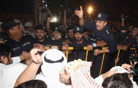 A policeman gestures at Kuwaiti demonstrators during an anti-government protest in front of the parliament in Kuwait City, October 15, 2012. REUTERS/Mohammed Jassim