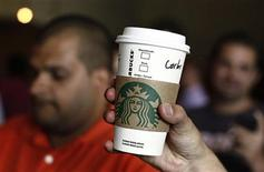 A Starbucks employee holds up a cup of coffee at a Starbucks coffee store in San Jose June 20, 2012. REUTERS/Juan Carlos Ulate