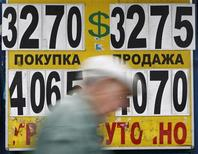 Мужчина проходит мимо пункта обмена валют в Москве, 31 мая 2012 года. Рубль подорожал утром вторника, отразив позитивную динамику нефти и пары евро/доллар, индексов и товарных валют; далее влияние будут оказывать также и внутренние корпоративные денежные потоки на фоне низкой спекулятивной активности из-за глобальной неопределенности в связи с нерешенными проблемами еврозоны. REUTERS/Maxim Shemetov