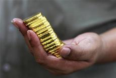 Работник завода компании PT Antam Tbk в Джакарте держит слитки золота, 13 июля 2012 года. Золотодобывающий Петропавловск увеличил добычу золота на 11 процентов за девять месяцев 2012 года в годовом исчислении в основном за счет рудников Албын и Маломыр в Амурской области, сообщила компания во вторник. REUTERS/Beawiharta