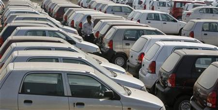An employee walks through parked cars at Maruti Suzuki's stockyard on the outskirts of the Ahmedabad March 1, 2011. REUTERS/Amit Dave/Files