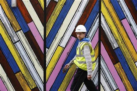A construction worker walks past a colourful hoarding in the city of London October 4, 2012. REUTERS/Luke MacGregor