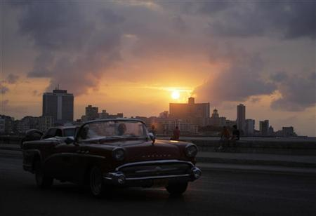 A car is driven on Havana's seafront boulevard 'El Malecon' at sunset March 13, 2012. REUTERS/Desmond Boylan