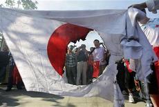 Демонстранты держат частично сожженный флаг Японии во время антияпонских выступлений в Вухане, 16 сентября 2012 года. Китайский бюджетный авиаперевозчик Spring Airlines предлагает бесплатные билеты в Японию в надежде стимулировать спрос после того, как десятки путешественников отменили или отложили запланированные поездки на фоне территориального спора между двумя странами по поводу островов в Восточно-Китайском море. REUTERS/Stringer