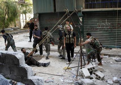 Members of the Free Syrian Army use a catapult to launch a homemade bomb during clashes with pro-government soldiers in the city of Aleppo, October 15, 2012. REUTERS/Asmaa Waguih