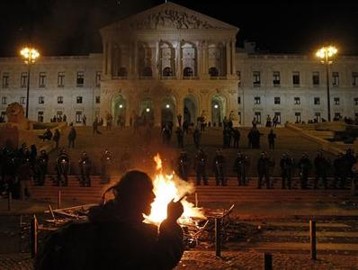 A man protests against the new 2013 state budget in front of the parliament as a fire burns in front of it in Lisbon October 15, 2012. REUTERS/Jose Manuel Ribeiro