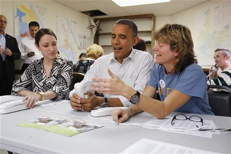 U.S. President Barack Obama (C) jokes about a telephone with campaign volunteers Alexa Kissinger (L) and Suzanne Stern as he makes calls from a campaign office in Williamsburg, Virginia, October 14, 2012. REUTERS/Jonathan Ernst