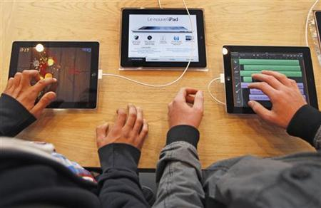Customers try iPad tablets on display at a new Apple store during its official oppening in Strasbourg September 15, 2012. REUTERS/Vincent Kessler