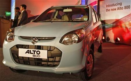 Officials stand next to the newly launched Maruti Suzuki Alto 800 car in Ahmedabad October 16, 2012. REUTERS/Amit Dave