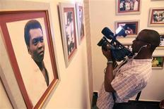 A videographer films photographs of Nigeria's music legend Fela Kuti during the opening ceremony of a museum in his honour in Lagos October 15, 2012. REUTERS/Akintunde Akinleye