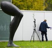 A police officer investigates the surroundings of Rotterdam's Kunsthal art gallery in the Netherlands October 16, 2012. REUTERS/Robin van Lonkhuijsen