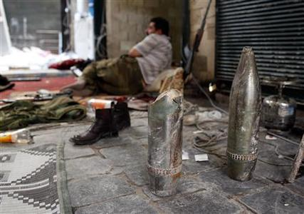 A member of the Free Syrian Army lies behind tank shells used by pro-government forces in the old part of Aleppo October 16, 2012. REUTERS/Asmaa Waguih