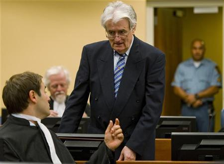 Former Bosnian Serb leader Radovan Karadzic talks to member of his legal team Marko Sladojevic in the courtroom on the first day of his defense against war crime charges at the International Criminal Tribunal for the Former Yugoslavia in The Hague October 16, 2012. REUTERS/ Robin van Lonkhuijsen
