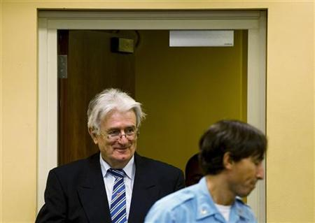 Former Bosnian Serb leader Radovan Karadzic enters the courtroom on the first day of his defense against war crime charges at the International Criminal Tribunal for the Former Yugoslavia in The Hague October 16, 2012. REUTERS/ Robin van Lonkhuijsen